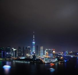 Shanghai Skyline of Pudong by night with boats on Huangpu river, 2011