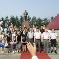 Visitor's group at village plaza with Mao statue at Maos birthplace village Shaoshan in Hunan province- brandeins