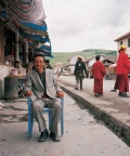 man sitting in front of his small shop,  while woman are taking care of the Yaks at the mountain top, Tagong Sichuan